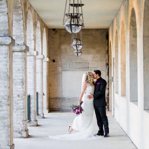 Bride and groom kiss outside of the Lightner Museum