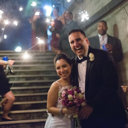 Bride and groom exit their wedding reception at the Lightner Museum